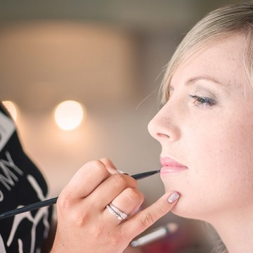 Becky applying lip liner on bride